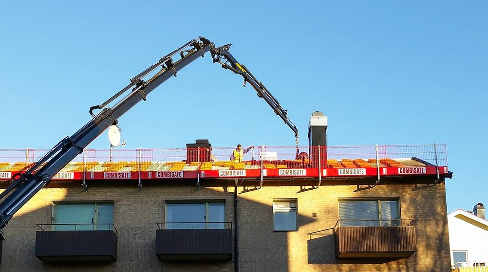 Kranbil som lyfter upp takpannor
